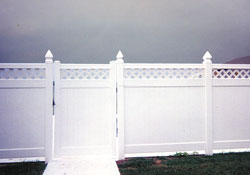 White fence with lattice and post caps